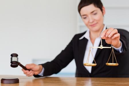 acomodador: Juez serio con un martillo y la escala de la justicia en su oficina