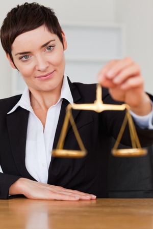 Woman holding the justice scale in her office photo