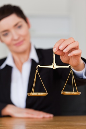 impartial: Serious woman holding the justice scale in her office Stock Photo