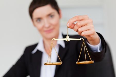 balanza justicia: Mujer de negocios serio la celebraci�n de la escala de la justicia con el enfoque de la c�mara sobre el objeto