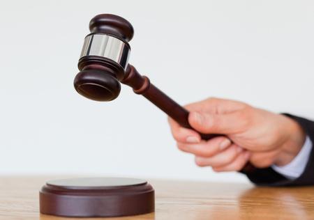 martillo juez: Mano golpeando un martillo sobre un fondo blanco Foto de archivo