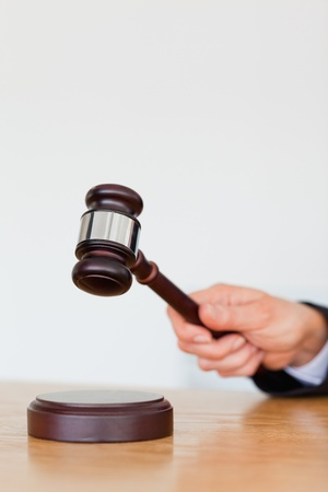 career fair: Portrait of a hand knocking a gavel against a white background