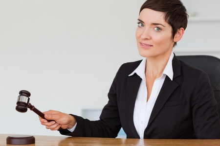Woman knocking a gavel in her office Stock Photo - 10784728