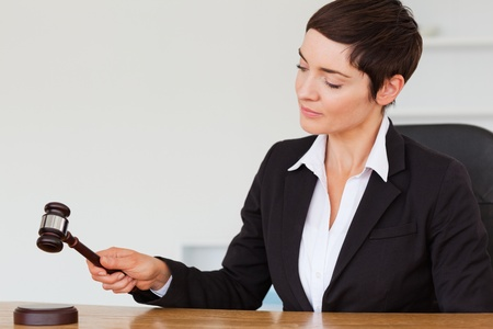 Serious woman knocking a gavel in her office Stock Photo - 10784762