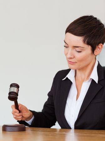Portrait of a woman knocking a gavel against a white background photo