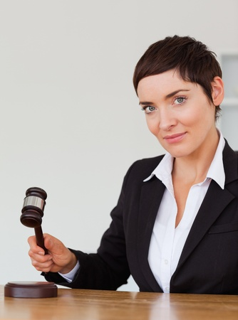 Portrait of a serious woman knocking a gavel in her office Stock Photo - 10780374