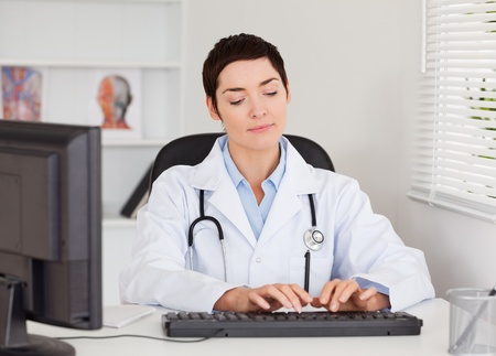 Doctor typing with her computer in her office photo