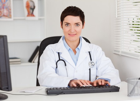 Female doctor typing with her computer in her office photo