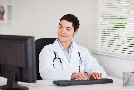 Charming doctor typing with her computer in her office photo