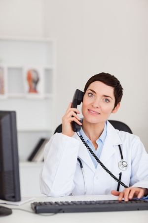 Portrait of a  smiling female doctor making a phone call in her office Stock Photo - 10780449