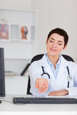 Doctor showing pills in her office Stock Photo - 10780376