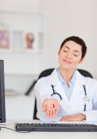 Portrait of a  young female doctor showing pills with the camera focus on the pills Stock Photo - 10791195