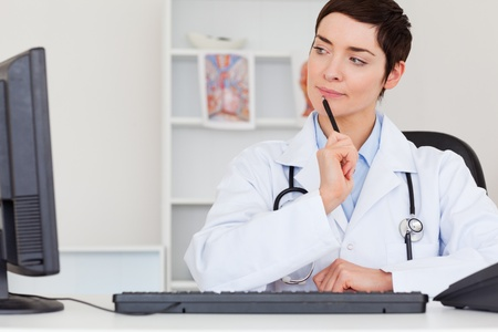 Thoughful female doctor in her office Stock Photo - 10784431