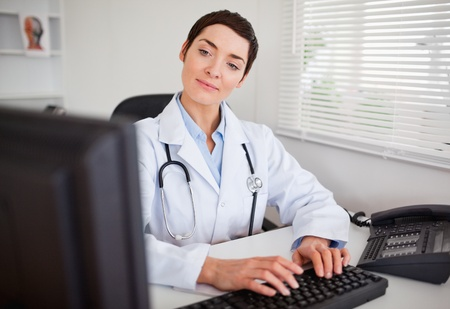 Cute doctor looking at her computer in her office photo