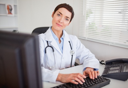 Cute female doctor typing with her computer in her office photo