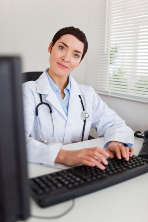 Portrait of a smiling female doctor typing with her computer in her office photo