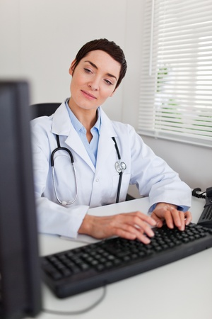 Portrait of a charming female doctor typing with her computer in her office photo