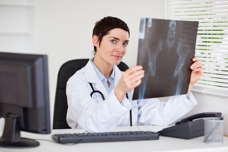 Professional female doctor holding a set of X-ray in her office photo
