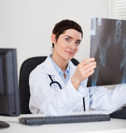 Focused female doctor holding a set of X-ray while lookinigat the camera photo