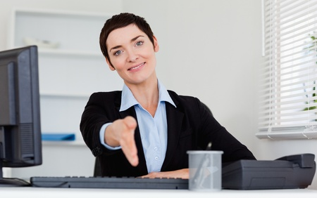 Charming business woman giving her hand while looking at the camera Stock Photo - 10917238