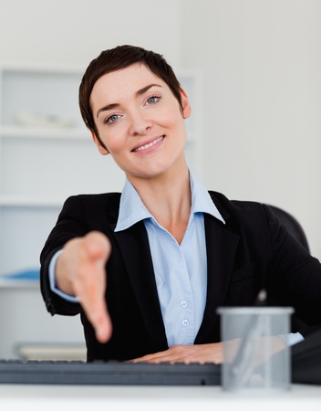 Portrait of a smiling business woman giving her hand while looking at the camera Stock Photo - 10917240