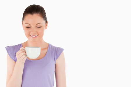 Lovely woman enjoying a cup of coffee while standing against a white background photo