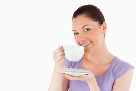 Cute woman enjoying a cup of coffee while standing against a white background photo