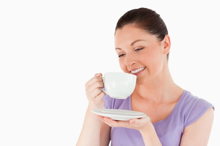 Gorgeous woman enjoying a cup of coffee while standing against a white background photo