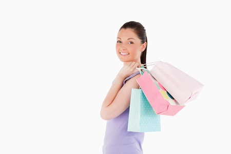 Charming woman holding shopping bags while standing against a white background photo