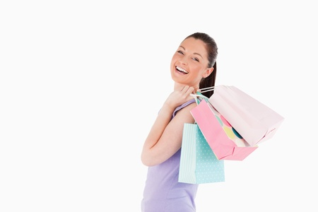 Beautiful woman holding shopping bags while standing against a white background photo
