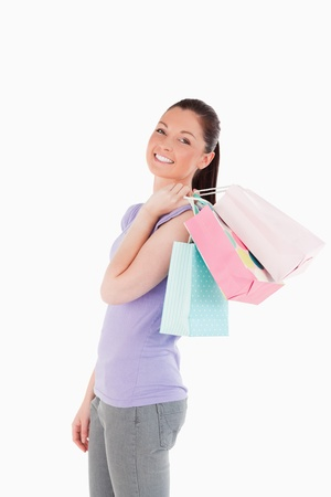 Good looking woman holding shopping bags while standing against a white background photo