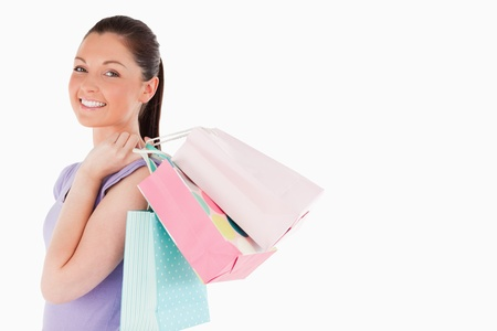 Attractive woman holding shopping bags while standing against a white background photo