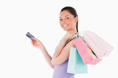 Attractive woman with a credit card holding shopping bags while standing against a white background photo