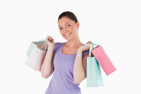 Pretty woman holding shopping bags while standing against a white background photo