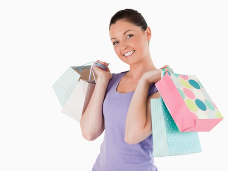 Gorgeous woman holding shopping bags while standing against a white background photo