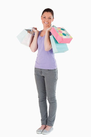Lovely woman holding shopping bags while standing against a white background photo