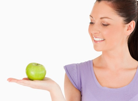 Charming woman holding an apple while standing against a white background photo