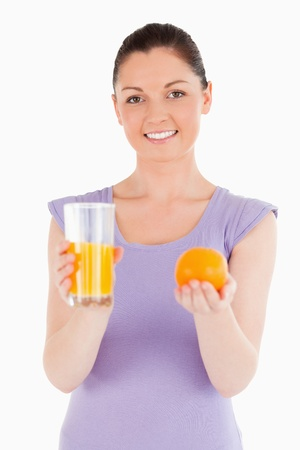 Portrait of an attractive woman holding an orange and a glass of orange juice while standing against a white background photo