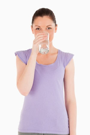 Charming woman drinking a glass of water while standing against a white background photo