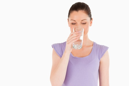 Beautiful woman drinking a glass of water while standing against a white background photo