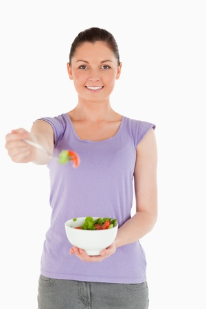Attractive woman holding a bowl of salad while standing against a white background photo