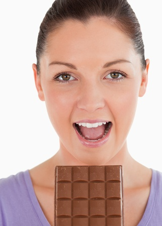 Portrait of an attractive woman eating a chocolate block while standing against a white background photo