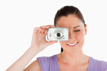 Portrait of a beautiful woman using a camera while standing against a white background photo