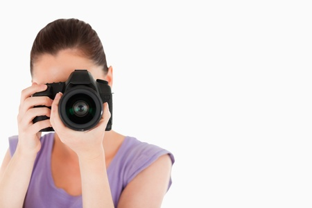 Beautiful female using a camera while standing against a white background photo