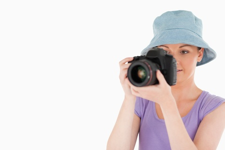 Lovely female using a camera while standing against a white background photo
