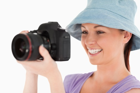 Cute female using a camera while standing against a white background photo