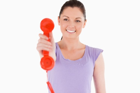 Good looking woman holding a red telephone while standing against a white background photo