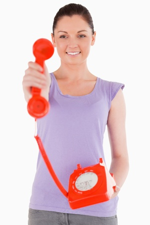 Charming woman holding a red telephone while standing against a white background photo