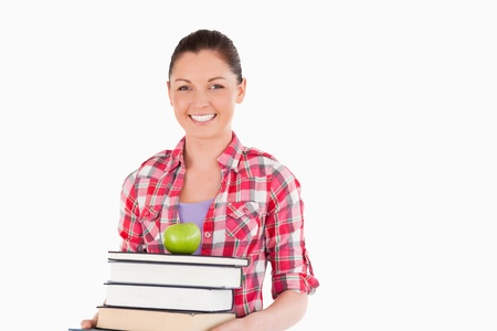 Beautiful female holding and a apple and books while posing against a white background photo