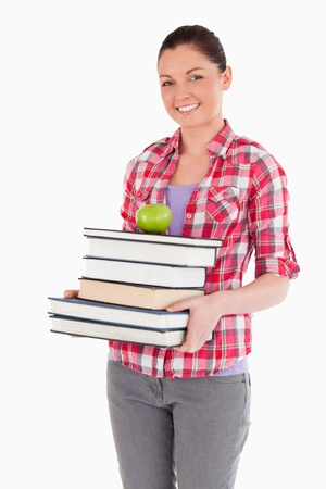 Attractive female holding and a apple and books while posing against a white background photo